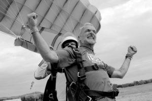 homme à l'atterissage d'un saut en parachute en PACA les bras en l'air avec la voile de parachute gonflée photo en noir et blanc